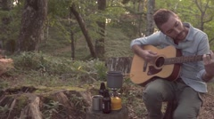 Slow motion footage of Caucasian man playing guitar at a camp site, Yamanashi Stock Footage