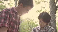 Slow motion footage of friends checking map at a camp site, Yamanashi Prefecture Stock Footage