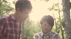 Slow motion footage of friends checking map at a camp site, Yamanashi Prefecture - stock footage