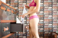 Woman searching for clothes in chest of drawers Stock Photos