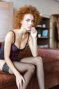 Tempting attractive woman in corset and stockings sitting on sofa Stock Photos