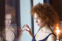Stock Photo of Tempting sensual young woman looking at the window