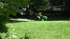 Tree leaves and park keeper drive lawn mower. 4K Stock Footage