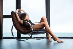 Sexy woman in lingerie relaxing on rocking chair Stock Photos