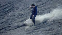 Young boy running down through volcano, super slow motion 240fps Stock Footage