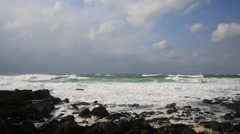 Angry waves breaking on the black rocks in the ocean of Jeju island Stock Footage