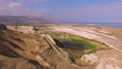 Aerial Israel. Fly over mountains of Arava desert, green salt lake Dead sea Stock Footage
