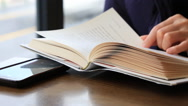 Stock Video Footage of Time lapse of Woman's hand reading a book in a cafe
