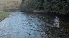Aerial shot of a man fly fishing in the River Tweed in the Scottish Borders Stock Footage