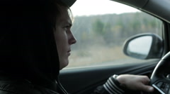 Serious young man is driving a car. Close-up Stock Footage