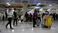 Woman cleaning the floor and people walking around Jeju island airport Stock Footage