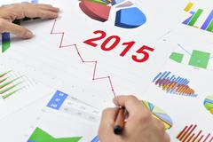 Businessman observing a chart with a downward trend during 2015 Stock Photos