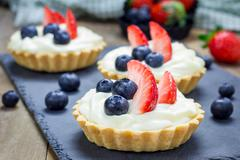 Stock Photo of Homemade shortbread tartlets with custard cream, strawberry and blueberry
