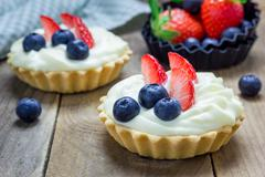 Homemade shortbread tartlets with custard cream, strawberry and blueberry Stock Photos