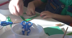 Little Boy Educator are Decorating a Triangle Painted in Green Decorating with Stock Footage