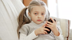 Cute little girl playing with smartphone Stock Footage