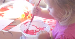 Small Blonde Girl is Blending a Bright Pink Paint in a Plate by Brush Kid with Stock Footage