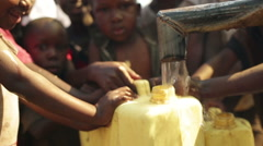 Children filling up a plastic container at a water well in Rural Uganda, Africa - stock footage