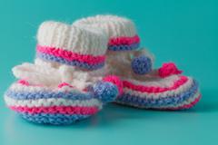Newborn boy announcemet. Knitted booties on bright aquamarine background - stock photo