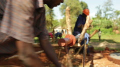An African man going into a hole to build a water well in rural Uganda - stock footage