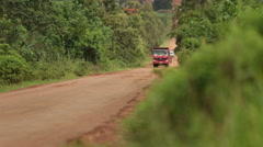 A truck going down a dirt road in rural Africa Stock Footage