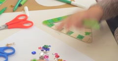 Kids Hands Are Removing a Heap of Sequins Decorating a Green Triangle Hands Stock Footage
