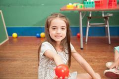 Girl holding a plastic ball Stock Photos