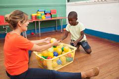Teacher playing with a little student Stock Photos