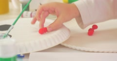 Childish Hand is Putting a Small Red Balls Plate White Disposable Dish Making a - stock footage