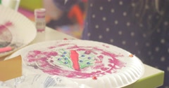 Kid is Painting by Paints on a Disposable Dish White Plate Painting a Clock by Stock Footage