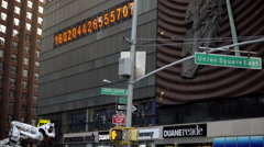 famous numbers ticker in Union Square panning flow of traffic cars and taxi cabs - stock footage