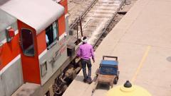 Man packs luggage into a train in the New Delhi Railway Station in India. Stock Footage