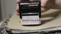 'Worthless' written on a stamp over big folder of paperwork - stock footage