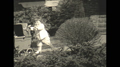 Vintage 16mm film, 1934, New Jersey, toddler playing with pram Stock Footage