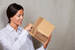 Stock Photo of Toothy smile woman standing and opening parcel in formal clothing on grey tex
