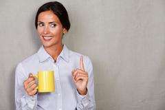 Stock Photo of Straight hair lady smiling with toothy smile pointing up while holding mug in