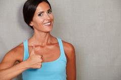 Stock Photo of Healthy female showing thumb up and smiling with toothy smile while looking a