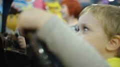 The boy turns the steering wheel in racing simulator Stock Footage