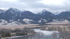 Wide shot of herd of elk crossing the Yellowstone river in winter Stock Footage