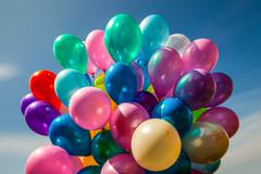 Multi-colored balloons on blue sky background - stock photo