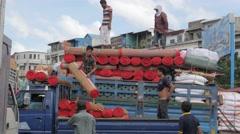Men unloading straw mats at the market,Phnom Penh,Cambodia Stock Footage