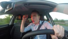 Young handsome man drives modern car - he listens to music - sings a song  Stock Footage