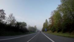 car passes through the forest on the two-lane road - view from car - stock footage