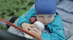 Boy with a milk bottle in a carriage Stock Footage