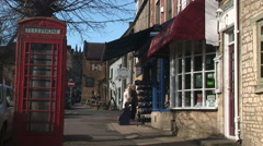 Cotswolds England telephone box people shopping in tourist destination england - stock footage