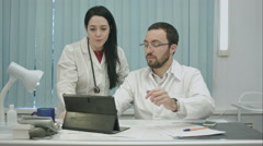 Male and female doctors discuss results useing tablet Stock Footage