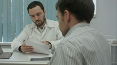 Male bearded doctor with tablet consult client Stock Footage