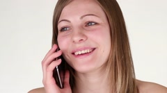 Funny and beautiful girl talking on a cell phone in the studio. - stock footage