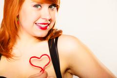 Gorgeous young woman holding candy heart. - stock photo