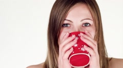 Beautiful girl drinks tea from a red mug. Stock Footage